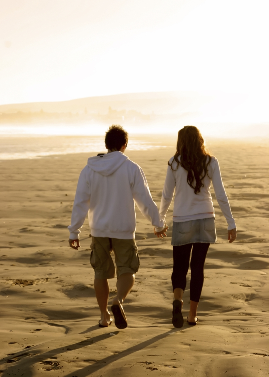 Young couple in love walking along a secluded beach